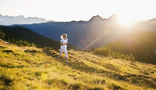 Austria --- Austria, Salzburg County, Young woman running in alpine meadow --- Image by © Hans Huber/Westend61/Corbis